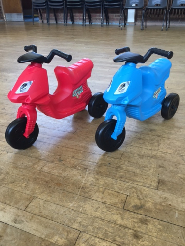 A pair of scooter trike ride-ons, one red and one blue