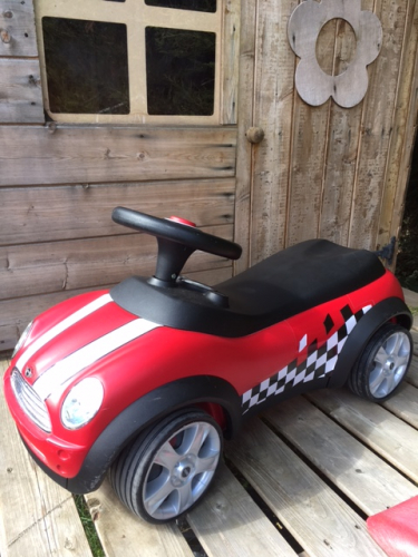 Red Mini ride on toy with racing stripes and chequered flag graphic.