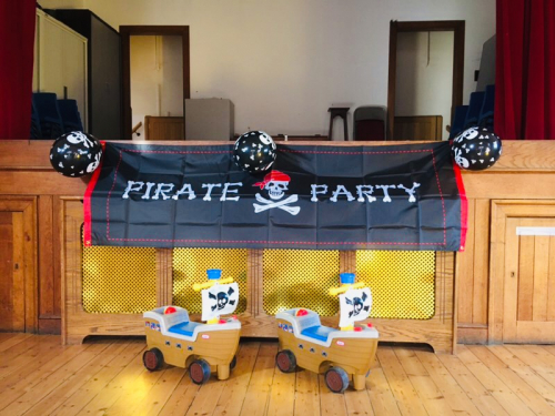 Two pirate ride on toys in front of a banner that says Pirate Party