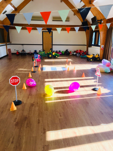 Ride on toys and a play road layout in a hall with sunshine